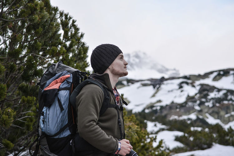 Side view of hiker with backpack while standing on snow covered mountain against sky