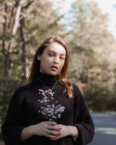 The Light Portrait Of A Woman Beautiful Woman Black Outfit Day Flower Focus On Foreground Front View Leisure Activity Lifestyles Nature Outdoors Park - Man Made Space Portrait Portrait Photography Purple Flower Standing Tree Young Women