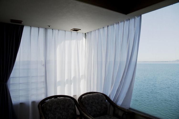 Japanese hotel room (Ryokan) Japanese Hotel Ocean View The Traveler - 2018 EyeEm Awards Absence Chair Curtain Hotel Room Hotel View Indoors  No People Sea Sky Sunlight Tranquility Water Window