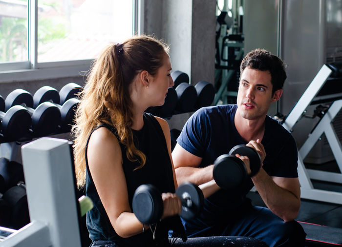 Trainer watching woman lifting dumbbell in gym