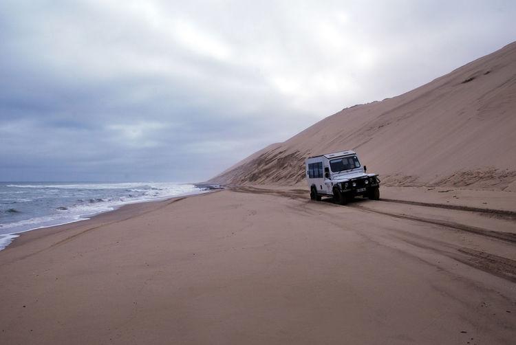 Car on desert by sea against sky