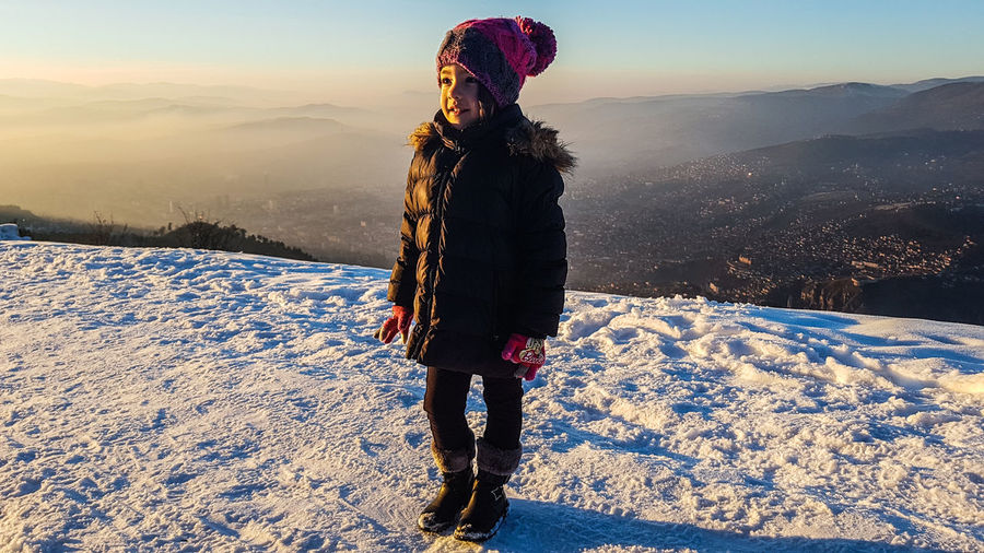 Cute girl standing on snow against sky during winter