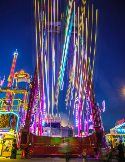 Low angle view of illuminated swing at stuttgart festival against sky at night