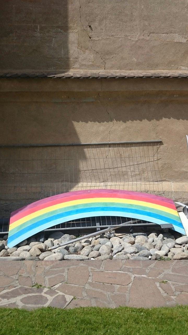 Rainbow Object On Stones By Wall