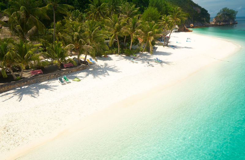 Crystal clear and turquoise sea water of the tropical sea . Background Bay Beach Beautiful Blue Calm Caribbean Coast Coastline Coconut Day Hot Idyllic Island Lagoon Landscape Malaysia Nature Nobody Ocean Outdoor Palm Paradise Plant Rawa Relax Resort Sand Scenery Scenic Sea Seascape Shore Sky Summer Sun Sunlight Sunny Tourism Tranquil Travel Tree Tropic Tropical Untouched Vacation Water