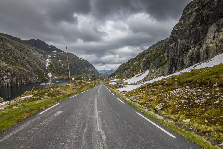 View on road against sky and mountains Norway Travel Cloud - Sky Day Diminishing Perspective Direction Dividing Line Environment Land Landscape Mountain Mountain Range Mountain Road Nature No People Non-urban Scene Outdoors Overcast Road Scenics - Nature Sky Storm The Way Forward Transportation