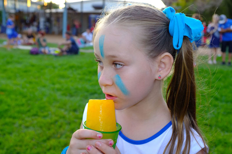 Girl With Face Paint Having Flavored Ice On Grassy Field