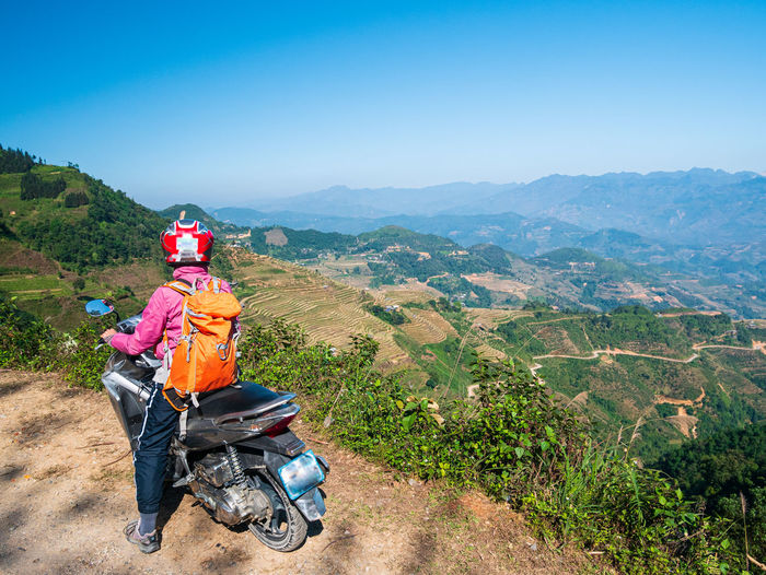 People riding motorcycle on mountain against sky