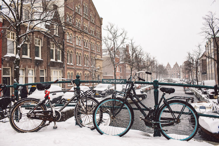 Bicycles on snow covered canal amidst buildings in city