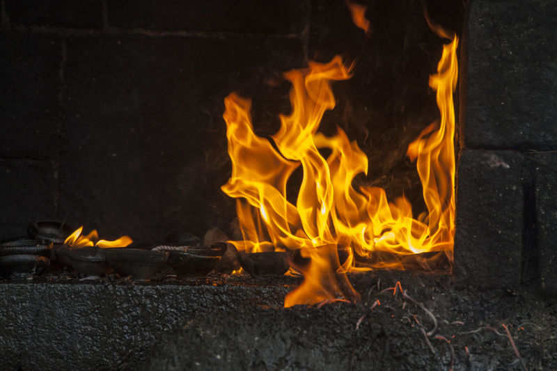 Close-up of fire on log at night