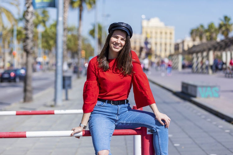 Front view of a smiling beautiful young woman wearing urban clothes sitting on a metallic fence while looking camera outdoors in the street in a bright day Smiling One Person Happiness Young Adult Leisure Activity Lifestyles Architecture Focus On Foreground Young Women Real People Portrait City Casual Clothing Front View Transportation Day Clothing Hair Looking At Camera Emotion Hairstyle Outdoors Beautiful Woman Woman Sitting Laughing Hat Urban Skyline Brunette Girl Teenager City City Life Cute Cool Modern Denim Jeans