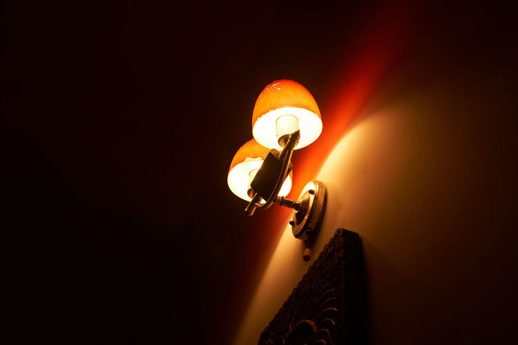 Low angle view of illuminated light bulbs in the dark