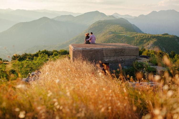 Couple on built structure against mountain range