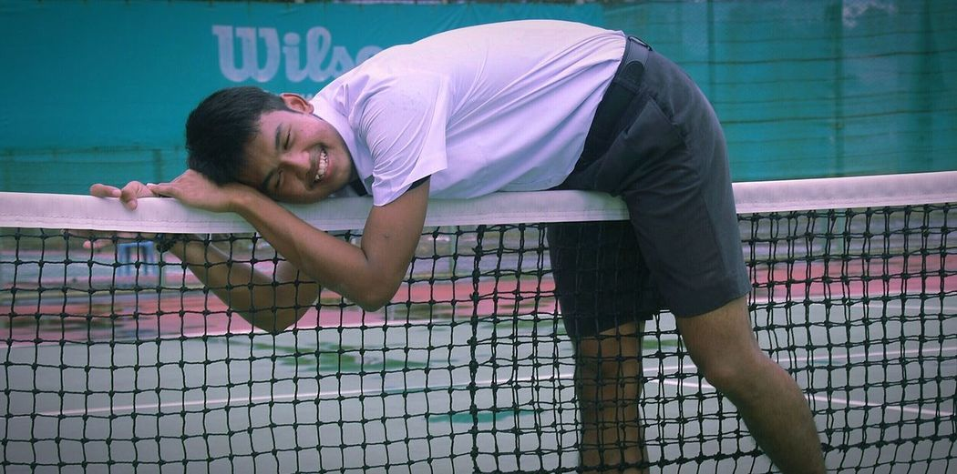 Male athlete leaning on tennis net on court