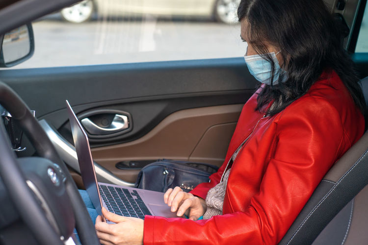 Rear view of woman using mobile phone while sitting in car