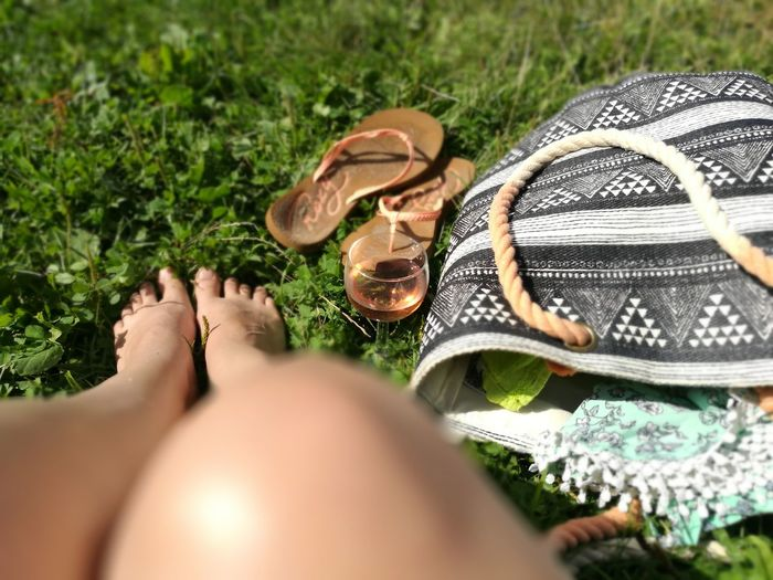 Low section of woman wearing shoes on grass