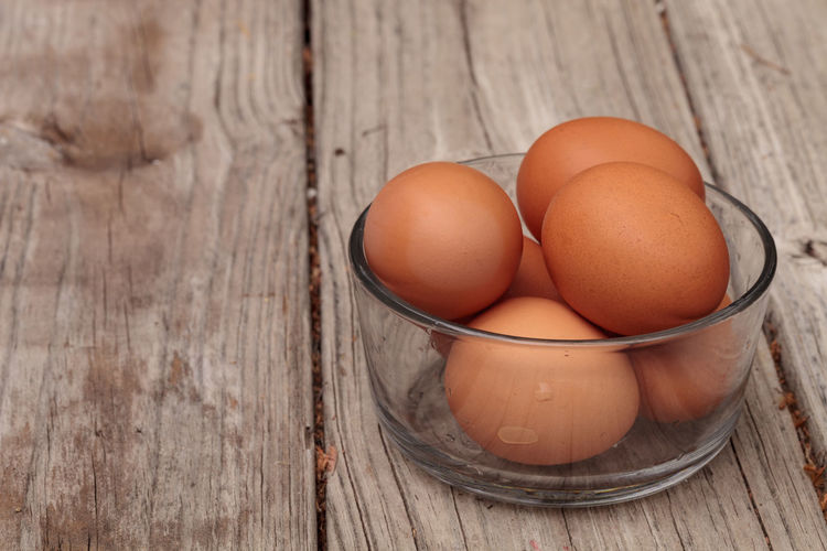 Fresh organic brown eggs in a clear glass bowl on a rustic farm picnic table in summer. Brown Chicken Egg Close-up Day Egg Egg Yolk Eggshell Farm Farm To Table Food Fragility Fresh Freshness Glass Bowl Healthy Eating Ingredient Natural No People Organic Poultry Table Wood - Material