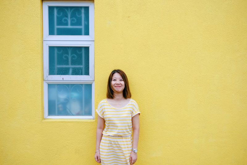 Same Color Ihaveathingforwalls Yellow One Person Women Architecture Wall - Building Feature Built Structure Smiling Looking At Camera Hairstyle Lifestyles Happiness Standing