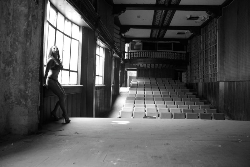 Lingerie model sitting on window sill at abandoned stage theater