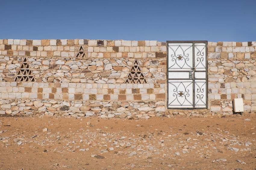 traditional build wall with door in town in north africa Wall Traditional Craft Door Africa Desert Horizontal Blue Sky Town Street Photography ArtWork Pattern, Texture, Shape And Form Bricks Rocks Traditional
