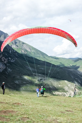 Rear view of people paragliding on mountain against sky
