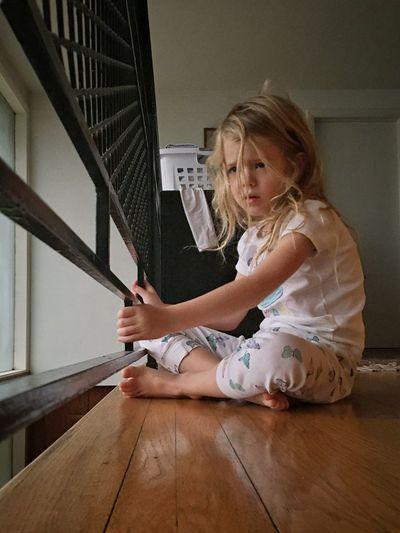 Girl Holding Railing While Sitting On Hardwood Floor At Home