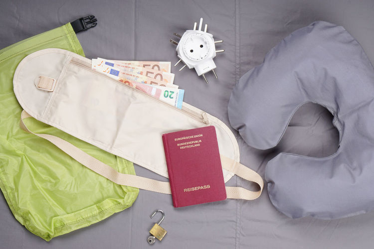 Directly Above Shot Of Currency With Passport And Neck Pillow On Seat