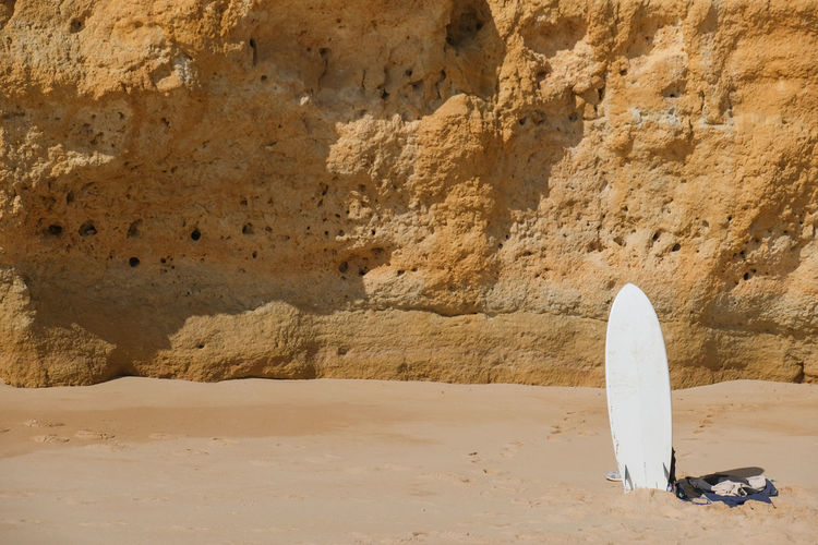 White surfboard in front of rock formation on beach