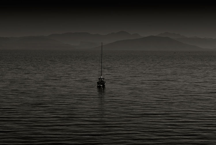 Silhouette of sailboat in sea against sky