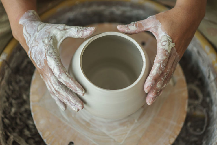 Cropped hands of woman making pottery in workshop