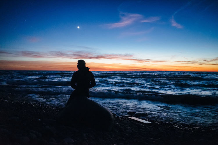 Man sitting on beach against sky during sunset