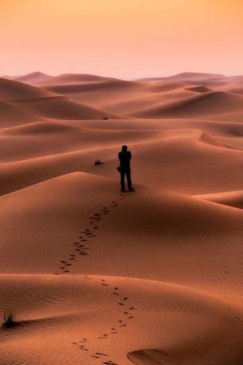 Mid distance view of silhouette man standing at desert during sunset