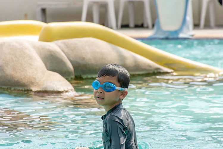 Asian boys are swimming in the pool. Water Childhood Child One Person Boys Males  Men Real People Pool Swimming Pool Swimming Day Portrait Leisure Activity Lifestyles Innocence Focus On Foreground Eyewear Outdoors Turquoise Colored