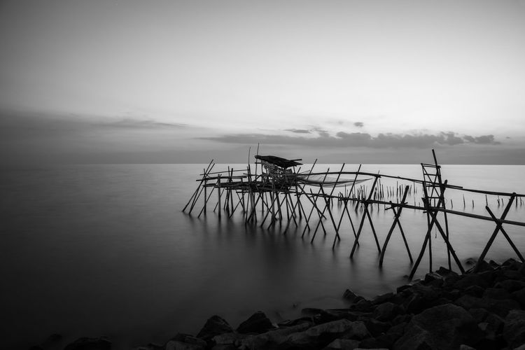 Wooden jetty at the rocky seaside during blue hour. Long Exposure Black and white. Water Sea Tranquil Scene Sky Scenics - Nature Tranquility Beauty In Nature Nature Pier Cloud - Sky Built Structure Architecture Non-urban Scene Idyllic Horizon No People Day Outdoors Horizon Over Water Long Exposure Black And White Calm
