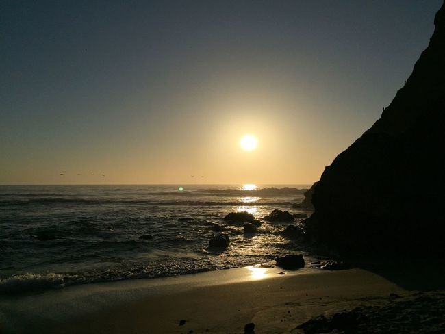 Sunset on the beach, California. Sea Water Horizon Tranquil Scene Beach Beauty In Nature Sun Sunset Tranquility Shore Rock - Object Nature Idyllic Rocks Sky Waves sunlight Seascape Remote Outdoors Sunbeam Travel Destinations Tourism Majestic Non Urban Scene Calm