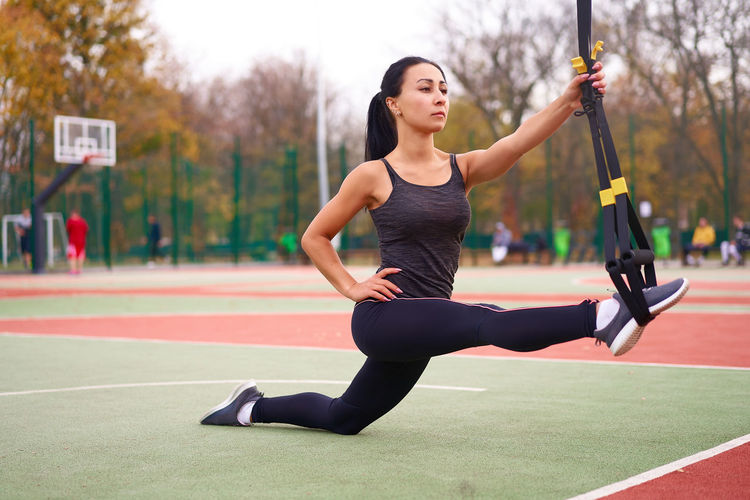 Full length of woman stretching at basketball court