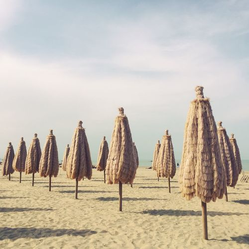 Panoramic view of umbrellas on beach against sky