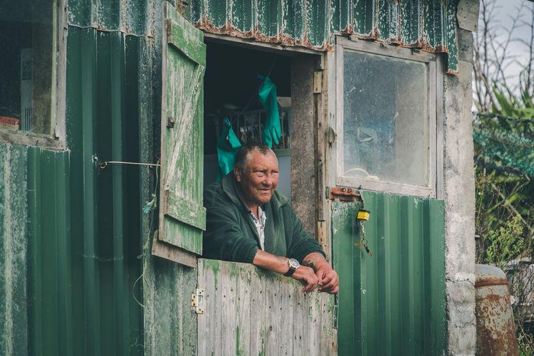Portrait of happy man standing by window