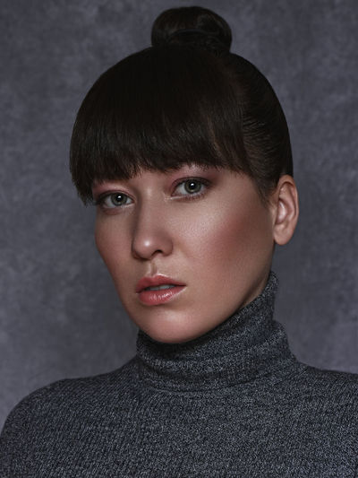 Portrait Headshot Looking At Camera Young Adult One Person Young Women Indoors  Close-up Front View Women Gray Background Lifestyles Gray Adult Beauty Real People Beautiful Woman Hairstyle Bangs Warm Clothing Turtleneck Human Face Nudemakeup