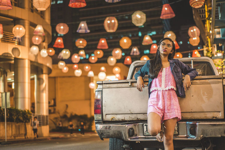 Teenage Girl Leaning On Pick-Up Truck At Illuminated Street