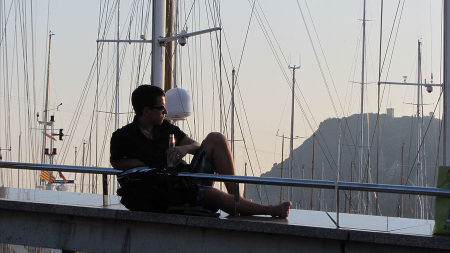 Full length of man with beer bottle resting on retaining wall by moored sailboats during sunset