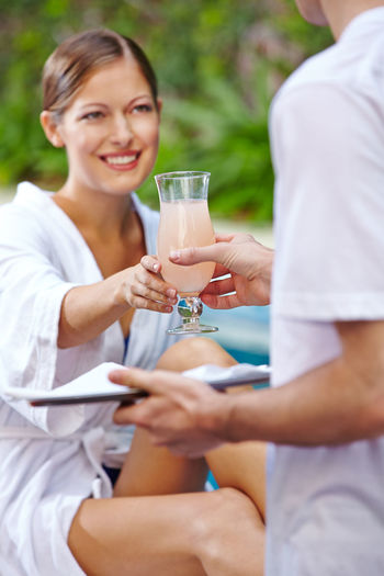 Midsection of a smiling young woman holding drink