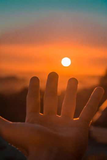 Close-up of hand against orange sky