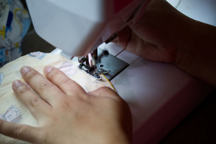 Midsection of person working on sewing machine