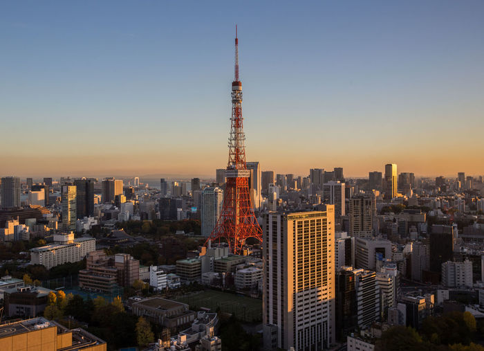Tokyo Tower Amidst Buildings In City Against Clear Sky During Sunset