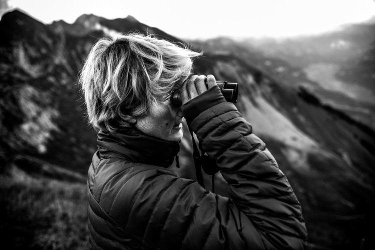 Man holding binoculars against mountain
