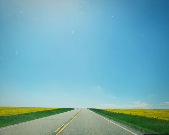 Empty road amidst land against blue sky