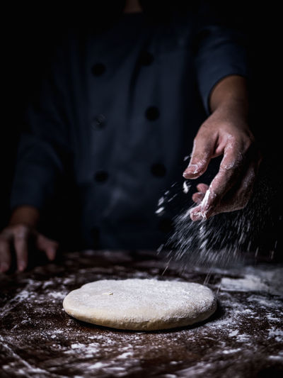 Baker - Occupation Bakery Chef Domestic Room Dough Flour Food Food And Drink Freshness Hand Homemade Human Body Part Human Hand Indoors  Midsection Occupation One Person Preparation  Preparing Food Sprinkling Sweet Food
