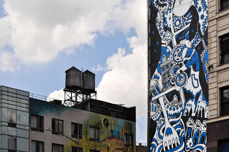 Low angle view of graffiti on building against sky
