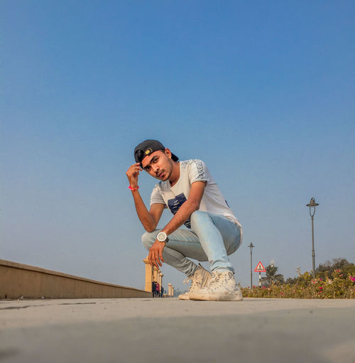Full length of man crouching on road against clear blue sky